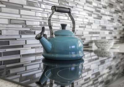 Image: blue kettle on induction hob against grey patterned wall ethical environmentally friendly
