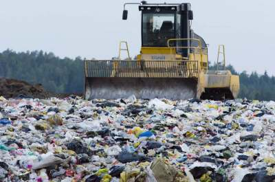 Image: landfill waste being pushed around by a machine