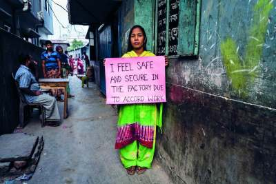 Image: bangladeshi garment worker holding sign that reads i feel safe and secure in the factory due to accord work