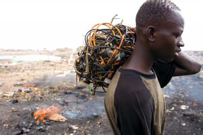 image: Ghanain man carrying electrical cables to reclaim wire