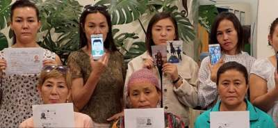 image: ughur women holding photos of their missing loved ones