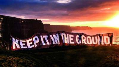 image: keep it in the ground protest banner with sunset