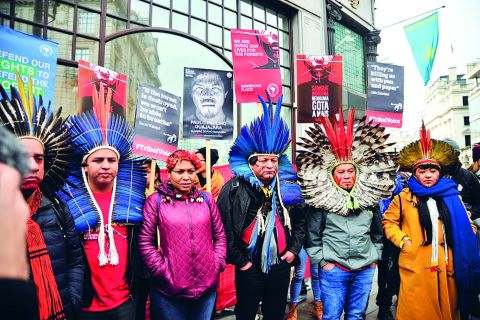 image: indigenous people in cultural dress protesting outside the brazilian embassy to remember amazon guardian paulo paulino