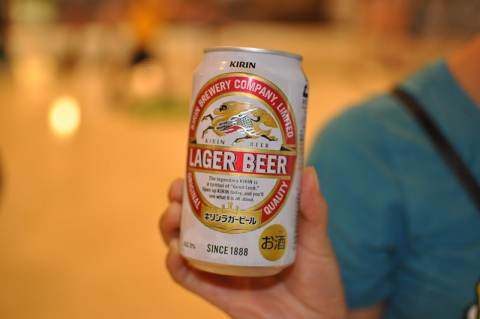 image: kirin beer can in focus in hand brooklyn lager donations burmese military
