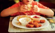 image: child's plate of chicken nuggets and chips unhealthy food