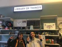 image: two smiling people in a library of things to share ethical consumer