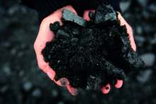 image: pink hands holding black coal