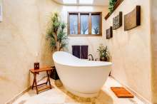 image: ethical bathroom with bowl bath and wooden features eco friendly plants