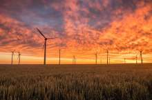 image: windmills against orange clouds sunset