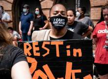 image: black lives matter masked protestor rest in power placard