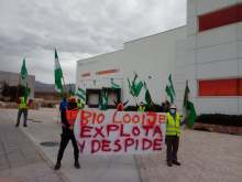 Workers protesting outside warehouse with banner