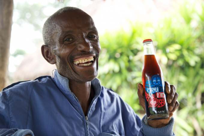 Image: karma cola is held by a smiling supplier