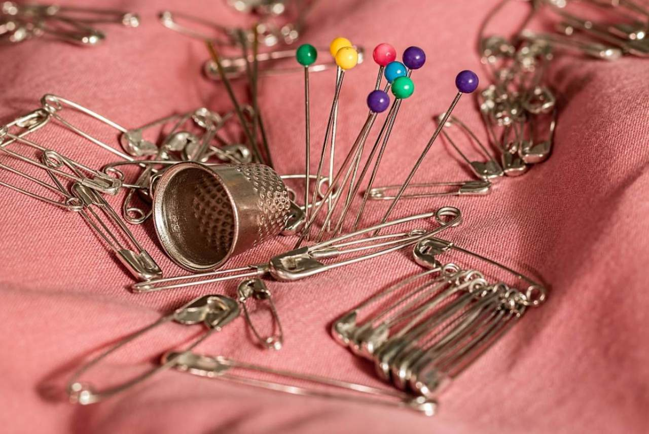 Image: pink cloth pinned together with pins and safety pin next to a thimble
