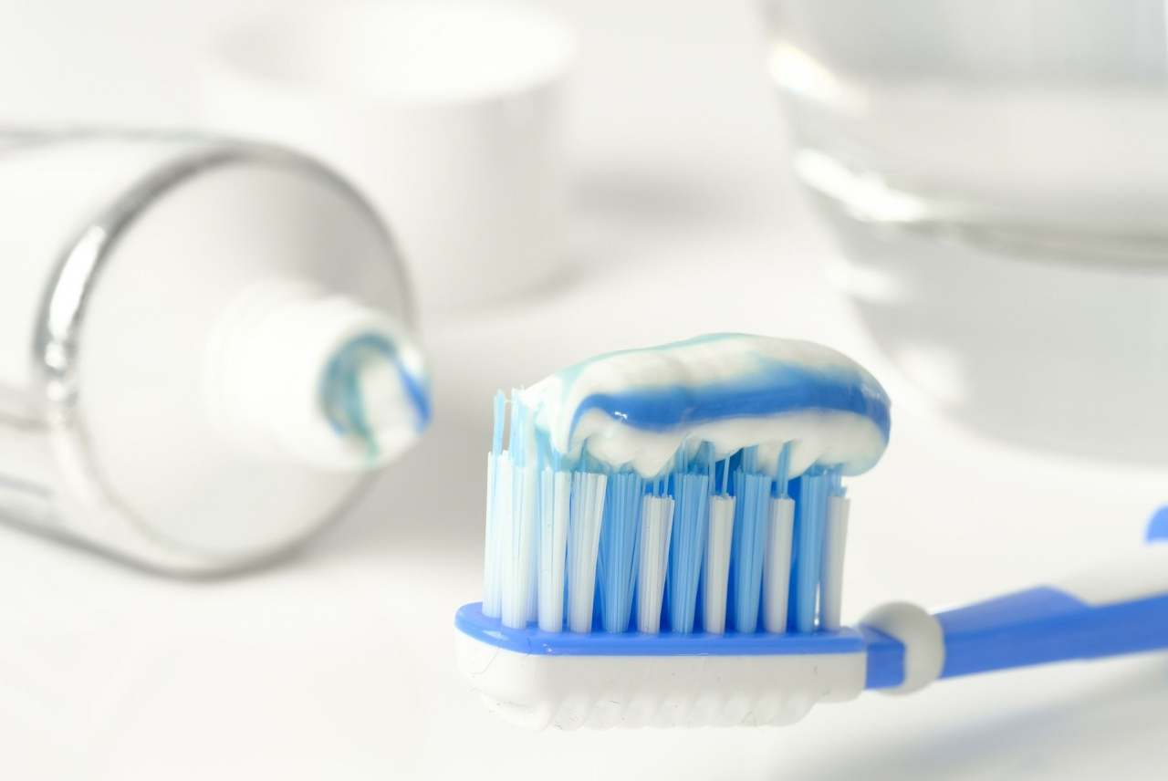 Image: blue and white toothpaste on blue and white toothbrush