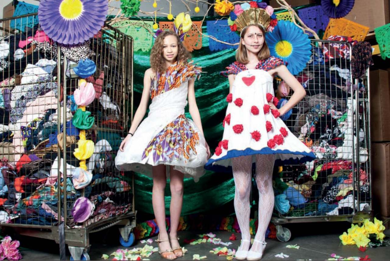 image: two students model dresses that they made from donated textile waste