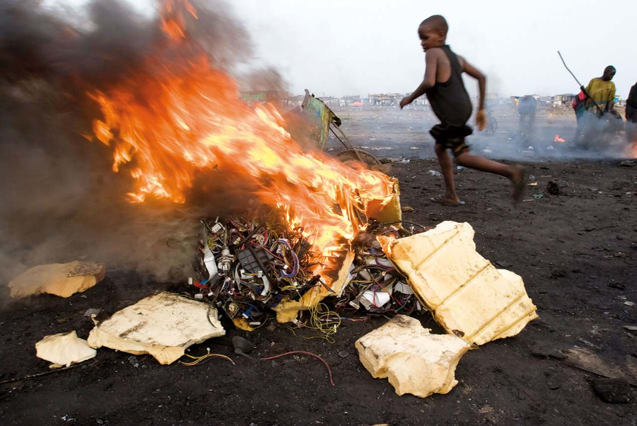 child in Accra, Ghana, runs next to a fire where electronic cables and other electrical components are being burned in order to melt off the plastic and reclaim the copper wiring