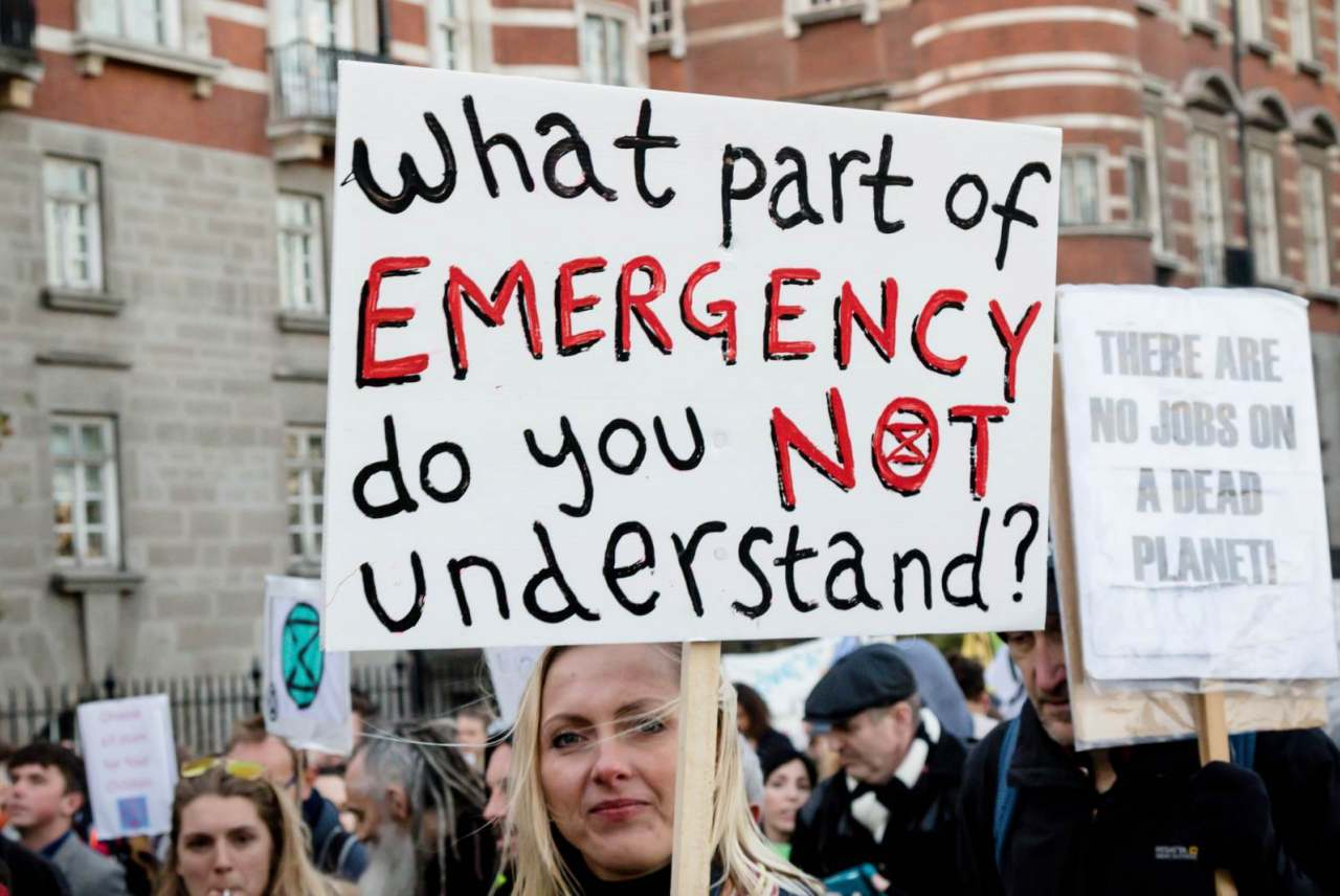 image: woman holding sign that reads what part of emergency do you not understand XR