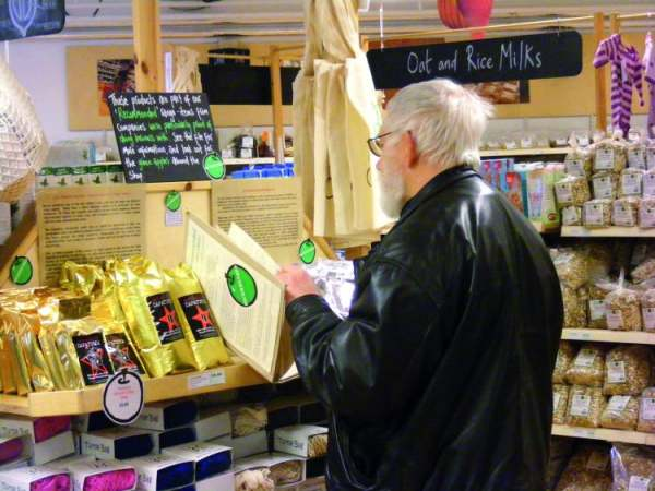 image: man looking at menu in unicorn our best rated supermarket in chorlton, manchester uk