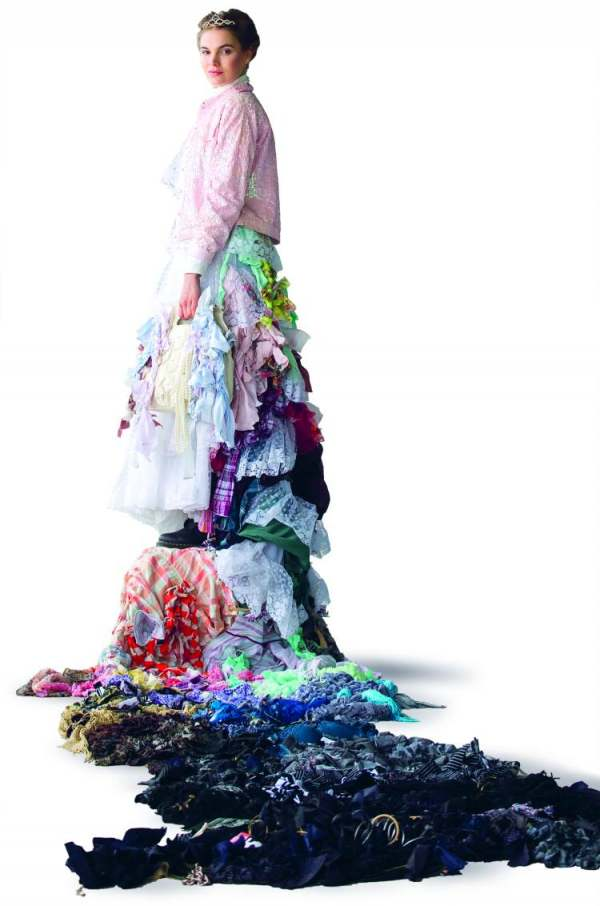 image: trash queen wears a train of used clothing to promote a buy nothing day greenpeace